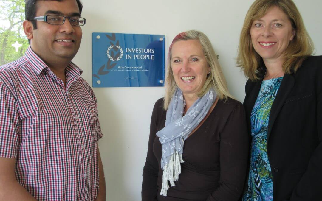 Smiling male and two females stand either side of plaque which announces their Investor in People award.